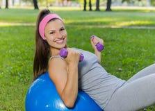 Ejercicio sonriente sano de la mujer joven de la aptitud en la bola de Pilates Fotos de archivo libres de regalías