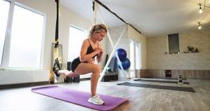 Ejercicios aeróbicos duros para estirar las piernas usando un elástico del funcionamiento en un estudio moderno que ella concentr metrajes