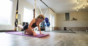 Ejercicios aeróbicos practicantes de la mujer rubia carismática que estiran el cuerpo y las piernas usando un elástico en un mode almacen de video