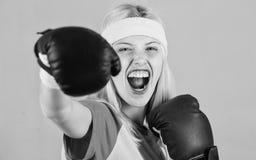 Ejercicios de encajonamiento cardiios para perder el peso Mujer que ejercita con los guantes de boxeo La muchacha aprende c?mo de imagenes de archivo
