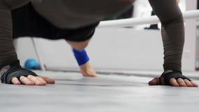 Ejercicios de entrenamiento de los pectorales del hombre del atleta en los puños en gimnasio Hombre del deporte que hace ejercici almacen de metraje de vídeo