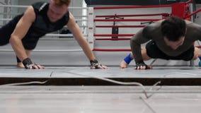 Ejercicios de entrenamiento de los pectorales del hombre del boxeador y manos que aplauden en gimnasio Combatientes que hacen emp metrajes