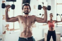 Ejercicios de la muchacha y de Guy In Gym Doing Dumbbells imagenes de archivo