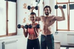 Ejercicios de la muchacha y de Guy In Gym Doing Dumbbells fotografía de archivo libre de regalías