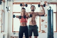 Ejercicios de la muchacha y de Guy In Gym Doing Dumbbells imagen de archivo libre de regalías