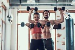 Ejercicios de la muchacha y de Guy In Gym Doing Dumbbells imagen de archivo