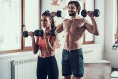 Ejercicios de la muchacha y de Guy In Gym Doing Dumbbells foto de archivo libre de regalías