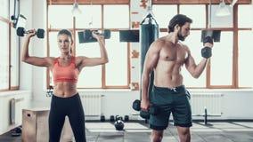 Ejercicios de la muchacha y de Guy In Gym Doing Dumbbells fotografía de archivo