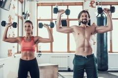 Ejercicios de la muchacha y de Guy In Gym Doing Dumbbells fotos de archivo
