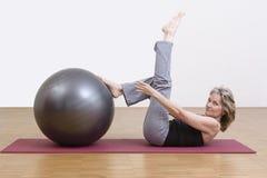 Ejercicios de la mujer con la bola de los pilates Foto de archivo