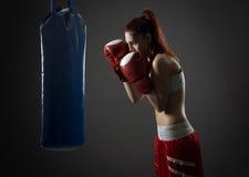 Ejercicios de la mujer del boxeo con el saco de arena imagen de archivo