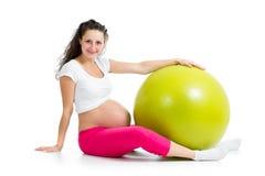 Ejercicios de la mujer embarazada con la bola del ajuste Foto de archivo libre de regalías