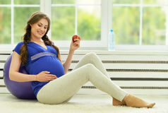 Ejercicios de la mujer embarazada con la bola gimnástica Fotos de archivo libres de regalías