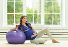 Ejercicios de la mujer embarazada con la bola gimnástica Imagenes de archivo