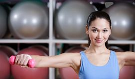 Ejercicios de la mujer joven con pesas de gimnasia Foto de archivo