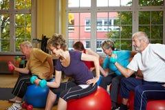 Ejercicios de la pesa de gimnasia en gimnasia Foto de archivo
