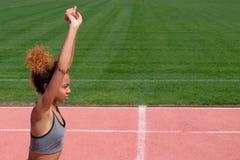 Ejercicios de los deportes y estirar o preparación de un corredor comenzar en el estadio Una muchacha afroamericana hermosa joven imagen de archivo