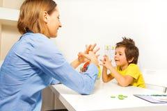 Ejercicios del muchacho que ponen los fingeres con el terapeuta Imagen de archivo