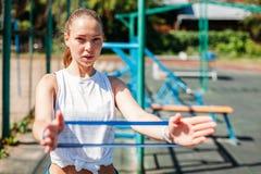 Ejercicios deportivos jovenes de la mujer con la goma al aire libre foto de archivo