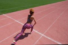 Ejercicios en el campo de deportes Una muchacha de piel morena joven en una camiseta gris, pantalones rosados y zapatillas de dep Foto de archivo libre de regalías