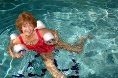 Ejercicios mayores de la piscina de la mujer fotos de archivo