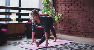 Ejercicios practicantes de la yoga de la señora de time lapse en casa en su sala de estar ella que lleva una ropa de deportes cóm almacen de video