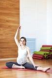 Ejercicios prenatales Mujer embarazada hermosa que ejercita mientras que se sienta en la posición de loto Fotos de archivo