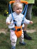 Ejercicios que caminan con el arnés de seguridad del niño Foto de archivo