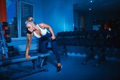 Ejercicios que hacen modelo de la aptitud atractiva con pesa de gimnasia Foto de archivo libre de regalías
