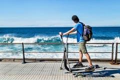 Ejercita al aire libre diario Ejercicios de trabajo del adolescente en el equipo y el océano del goce Fotografía de archivo libre de regalías