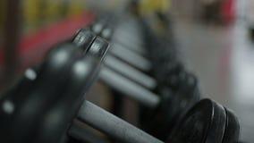 Ejercite el equipo preparado para el entrenamiento activo en el club de fitness, tiro del foco del estante almacen de metraje de vídeo