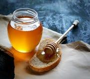Ejerza la actividad bancaria con la miel en una servilleta, un cazo de madera especial y el pan en un papel en un fondo azul Imagenes de archivo