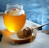 Ejerza la actividad bancaria con la miel en una servilleta, un cazo de madera especial y el pan en un papel en un fondo azul Imagen de archivo