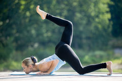 Eka Pada Ashtanga Namaskara. Beautiful sporty fit blond young woman in sportswear working out outdoors in park on summer day, doing variation of Caterpillar stock images