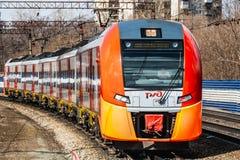 Ekaterimburgo, Sverdlovsk Rusia - 24 04 2019: El nuevo tren el?ctrico rojo y anaranjado Lastochka llega un nuevo ferrocarril del imagen de archivo libre de regalías