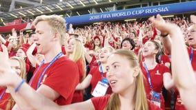 Ekaterinburg, Rusia - junio de 2018: Opinión los voluntarios del fútbol en el mismo baile uniforme rojo y azul marino y el canto almacen de video