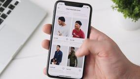 Ekaterinburg, Russia - 3 ottobre 2018: Uomo che usando Asos app sullo smartphone di iPhone X, passante in rassegna per i vestiti archivi video