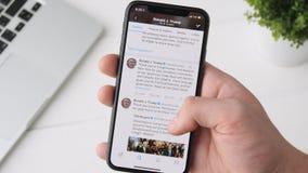 Ekaterinburg, Russia - 3 ottobre 2018: Uomo che usando Twitter app sullo smartphone di iPhone X, passante in rassegna attraverso  stock footage