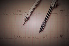 EKG printout and compasses. Under  monochromatic source Royalty Free Stock Photos