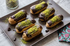 Chocolate Eclairs / Donut with pistachio powder Stock Photography