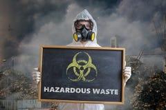 Ekologi- och föroreningbegrepp Mannen i overaller varnar mot farlig avfalls Arkivfoton
