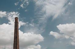 Ekologia i czysty nastrojowy zagadnienie - Fajczana fabryka z niebieskim niebem i chmurami w słonecznym dniu fotografia stock