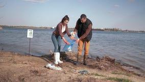 Ekologia, para wolontariuszów aktywiści czyści w górę zanieczyszczającego rzecznego bulwaru od plastikowego grata i zbierającego  zbiory
