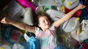 Ekologibegreppet, stoppar plast- Barnet vaknade upp och smiskade i en hög av plast- avfall, plast- förorening av planeten arkivfilmer