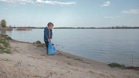 Ekologiczna puryfikacja natura, dziecko chłopiec ciągnie ciężką torbę grat na wskazywać znaka na rzeki plaży po czyścić w górę zdjęcie wideo