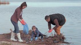 Ekologicznej katastrofy, kobiety i samiec wolontariuszi z dziecko chłopiec, zbierają klingerytu i polietylenu grat na plażowy pob zbiory wideo