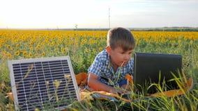 Ekologicznie życzliwy, dziecko pokazuje ręka gest jak pobliscy słoneczni photovoltaic panel na tła polu, chłopiec uses zdjęcie wideo