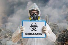 Ekologii i zanieczyszczenia pojęcie Mężczyzna w coveralls ostrzega przeciw biohazard odpady Zdjęcia Stock