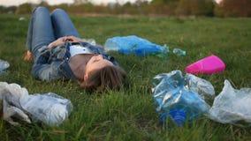 Ekologisk katastrof, plast- förorening av planeten En kvinna ligger på gräset i mitt av plast- avskräde och stock video