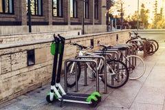 Ekologisk och personlig transport i stad Cykel och elektrisk sparkcykel arkivfoton